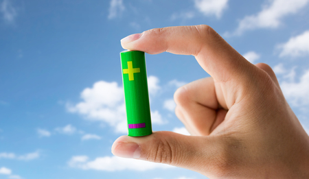 recycling, energy, power, environment and ecology concept - close up of hand holding green alkaline battery over blue sky and clouds background