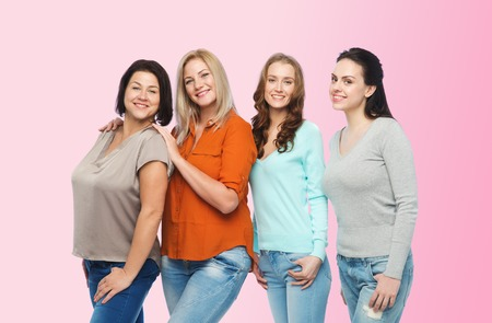 women friendship: friendship, fashion, body positive, diverse and people concept - group of happy different size women in casual clothes over pink background