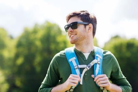 mochila de viaje: viajes, senderismo, excursionismo, el turismo y el concepto de la gente - hombre joven feliz en gafas de sol con mochila caminando al aire libre Foto de archivo