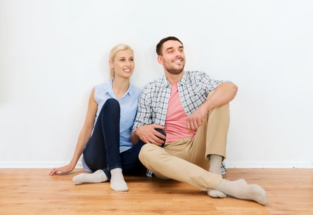 woman sitting floor: home, people, repair, moving and real estate concept - happy couple sitting on floor at new place