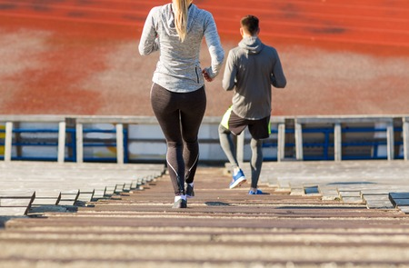 downstairs: fitness, sport, exercising and lifestyle concept - close up of couple running downstairs on stadium