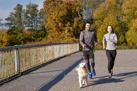 personas corriendo: fitness, deporte, la gente y el estilo de vida concepto - feliz pareja con perro corriendo al aire libre