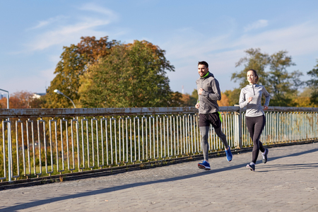 sport fitness: fitness, sport, people and lifestyle concept - happy couple running outdoors