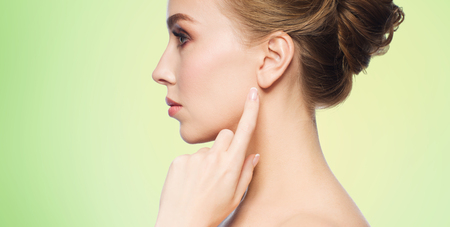 profile face: health, people and beauty concept - beautiful young woman pointing finger to her ear over green natural background