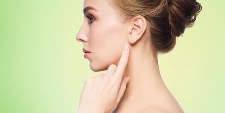 perfil de mujer rostro: la salud, las personas y el concepto de belleza - mujer joven y hermosa que señala el dedo a la oreja sobre fondo verde natural