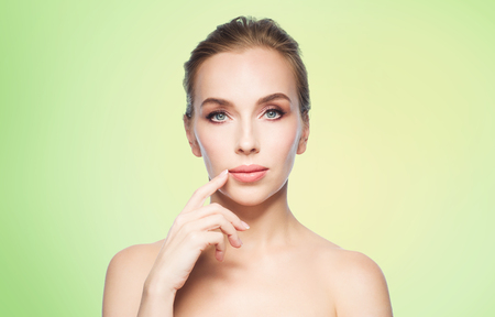 augmentation: beauty, people and plastic surgery concept - beautiful young woman showing her lips over green background