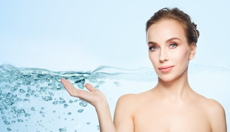 aqua naked: beauty, people, advertisement and health concept - smiling young woman holding something on palm of her hand over water splash bubbles on blue background Stock Photo
