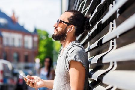 hombres jovenes: gente, música, tecnología, ocio y estilo de vida - hombre inconformista joven feliz con los auriculares y el teléfono inteligente en la calle de la ciudad