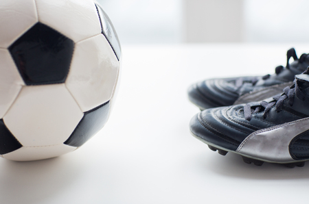 football cleats: sport, soccer, football and sports equipment concept - close up of ball and boots on table