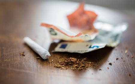substance abuse, nicotine addiction, drug sale and smoking concept - close up of marijuana joint and money Stock Photo