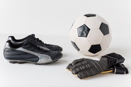 football cleats: sport, soccer, football and sports equipment concept - close up of ball, boots and goalkeeper gloves