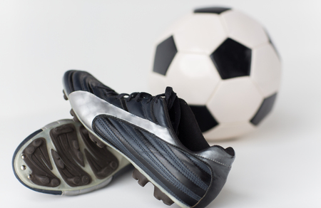 soccer boots: sport, soccer, football and sports equipment concept - close up of ball and boots