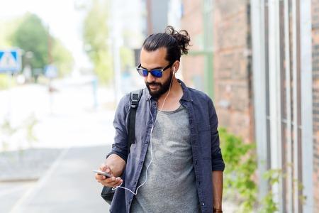 personas, tecnología, viajes y turismo - hombre con auriculares, teléfonos inteligentes y el bolso que recorre a lo largo de calle de la ciudad y escuchar música Foto de archivo
