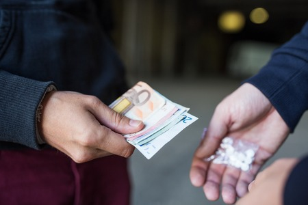 junky: drug trafficking, crime, addiction and sale concept - close up of addict with money buying dose from dealer on street