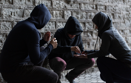 substance abuse, addiction and bad habits concept - close up of young people smoking cigarettes and using drugs outdoors Banque d'images