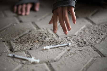 junky: substance abuse, addiction, people and drug use concept - close up of addict woman hands and used syringes on ground