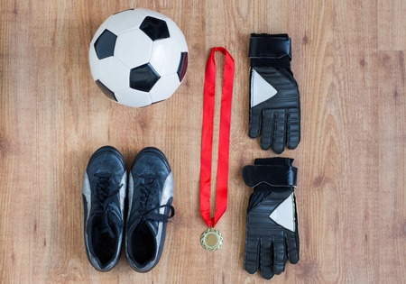 football boots: sport, achievement, championship and success concept - close up of soccer ball, football boots and goalkeeper gloves with golden medal on wooden background
