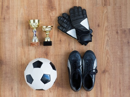 football boots: sport, achievement, championship and success concept - close up of soccer ball, football boots and goalkeeper gloves with golden cups on wooden background