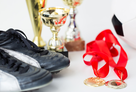 soccer boots: sport, achievement, championship and success concept - close up of football or soccer boots with golden medals and cups