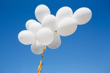 birthday decoration: holidays, birthday, party and decoration concept - close up of inflated white helium balloons in blue sky