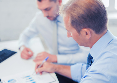 businesss and office concept - businessmen with notebook discussing graphs on meeting Stock Photo
