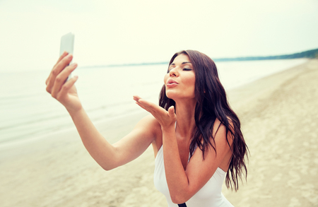 beach kiss: summer, travel, technology and people concept - sexy young woman taking selfie with smartphone and sending blow kiss on beach