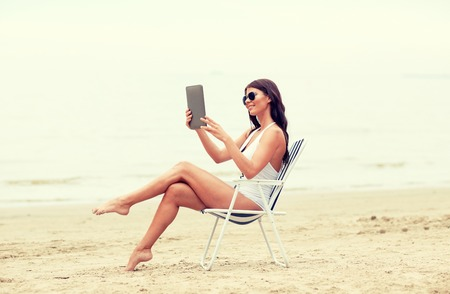 summer vacation, tourism, travel, holidays and people concept - smiling young woman with tablet pc computer sunbathing in lounge or folding chair on beach Stock Photo - 63352960