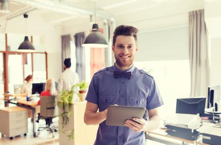 empleado de oficina: negocio, puesta en marcha y la gente concepto - hombre de negocios feliz o creativo empleado de oficina masculino con ordenador Tablet PC Foto de archivo