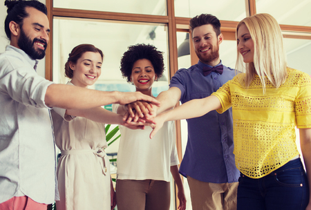 teamwork concept: business, startup, gesture, people and teamwork concept - happy creative team with hands on top of each other in office