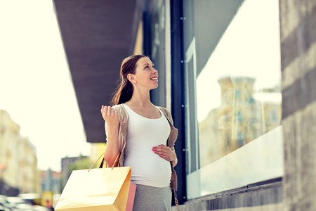 motherhood: pregnancy, motherhood, people and expectation concept - happy smiling pregnant woman with shopping bags at city street Stock Photo