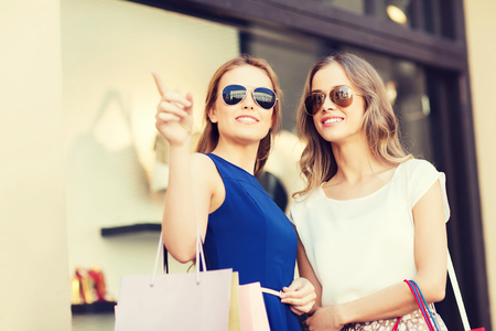 sale, consumerism and people concept - happy young women with shopping bags pointing finger at shop window in city Stock Photo