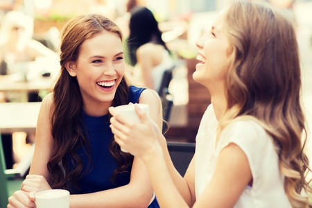 communication and friendship concept - smiling young women with coffee cups at cafe