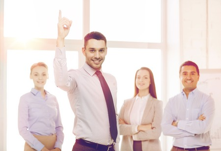 directing: business and office concept - smiling handsome businessman with team in office and finger up