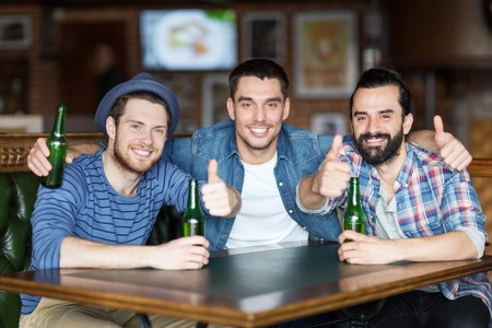 bottled beer: people, leisure, friendship, gesture and bachelor party concept - happy male friends drinking bottled beer and showing thumbs up at bar or pub Stock Photo