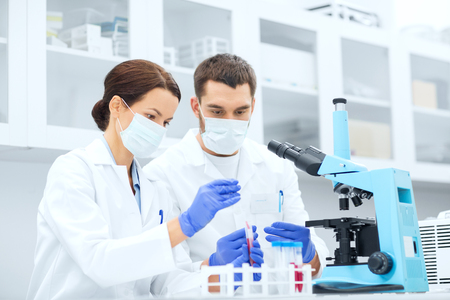 clinical: science, technology, biology and people concept - young scientists with pipette, test tube and microscope making research in clinical laboratory