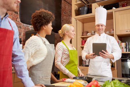 food technology: cooking class, culinary, food, technology and people concept - happy friends with tablet pc in kitchen