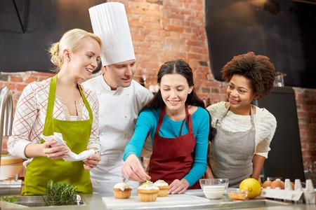 cooking class, culinary, bakery, food and people concept - happy group of women and male chef cook baking in kitchen photo