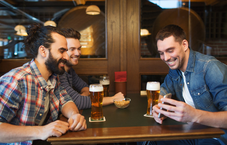 pubs: people, leisure, friendship, technology and bachelor party concept - happy male friends with smartphone drinking beer at bar or pub