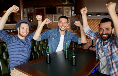bottled beer: people, leisure, friendship and bachelor party concept - happy male friends drinking bottled beer and having fun at bar or pub