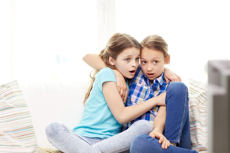 telly: people, children, television, friends and friendship concept - two scared little girls watching horror on tv at home