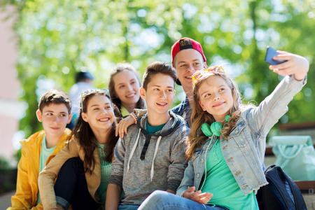 l'éducation, l'école secondaire, la technologie et les gens concept - groupe heureux étudiants ou amis adolescents prenant selfie par téléphone intelligent Banque d'images