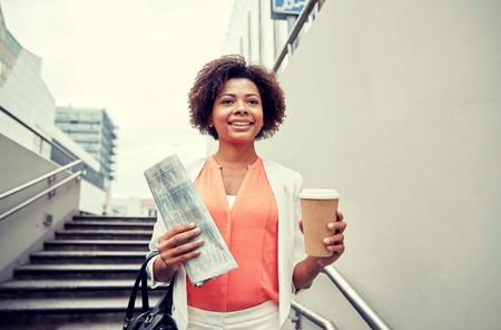 bajando escaleras: negocios y concepto de la gente - joven sonriente africano americano de negocios con la taza de café bajando escaleras en paso subterráneo de la ciudad