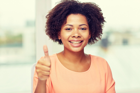 women smiling: people, ethnicity, gesture and leisure concept - happy african american young woman showing thumbs up at home Stock Photo