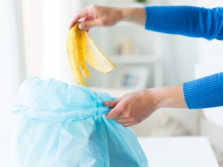 peel: recycling, food waste, garbage, environment and ecology concept - close up of hand putting banana peel into rubbish bag at home