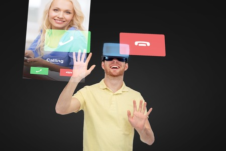 entertainment background: 3d technology, virtual reality, communication, entertainment and people concept - man in virtual reality headset or 3d glasses playing game over black background with incoming call on screens Stock Photo