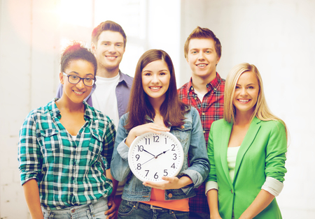 education and time concept - group of students at school with clock Stock Photo