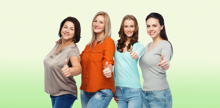 green clothes: friendship, fashion, body positive, gesture and people concept - group of happy different size women in casual clothes showing thumbs up over green natural background Stock Photo