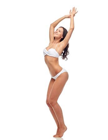cuerpo femenino: gente, moda, trajes de baño, verano y concepto de la playa - mujer joven feliz posando en el baile blanco traje de baño bikini con las manos levantadas