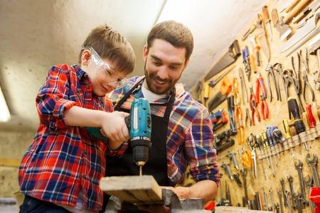familie, timmerwerk, houtwerk en mensen concept - vader en zoontje met boor perforeren houten plank op workshop