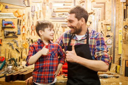 family, carpentry, woodwork, gesture and people concept - happy father and little son making thumbs up at workshop Stock Photo